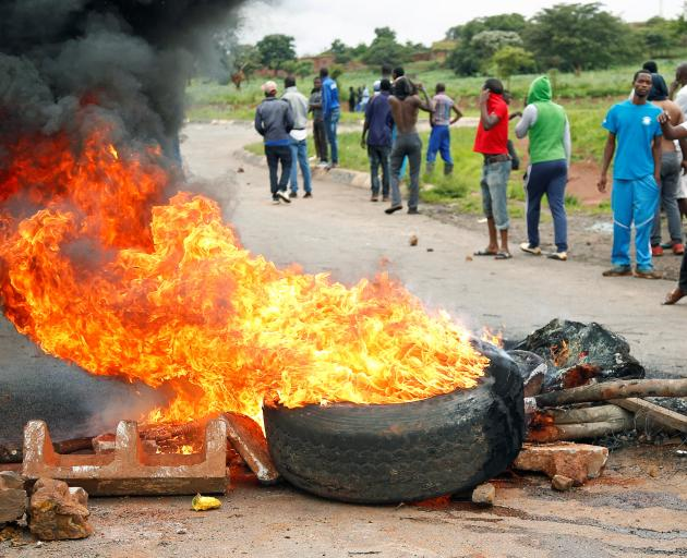 Protesters stand behind a burning barricade on a road leading to Harare. Photo: Reuters