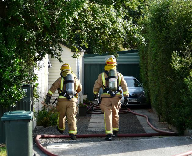 Firefighters enter a Balclutha property to assess the state of a solar system battery fire yesterday morning. Photo: Richard Davison