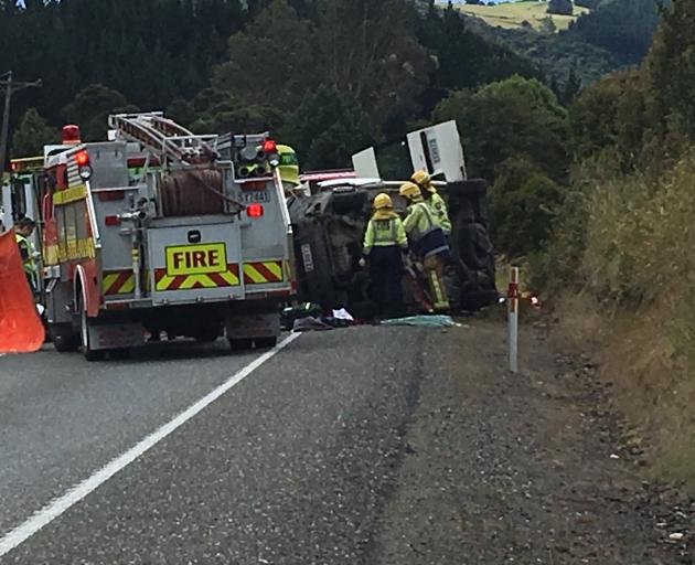 Fire and emergency vehicles attempt to free the occupant of a rolled campervan near Waitati....