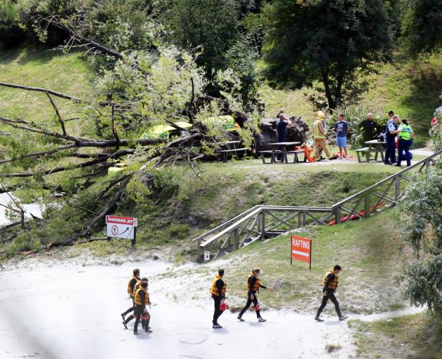 Emergency services work around a downed tree, as rafters return from a trip.