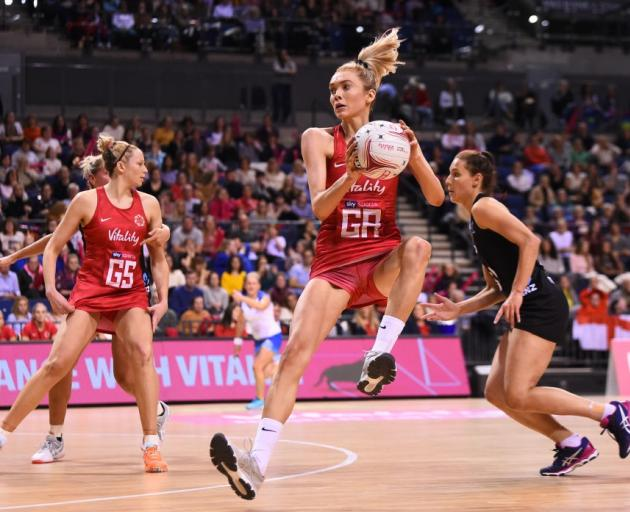 England's Helen Housby catches the ball as Silver Ferns defender Karin Burger trails her during...