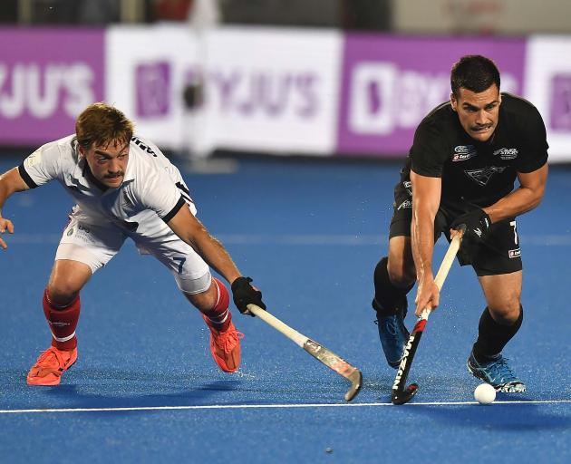 Nick Ross (right), of New Zealand, keeps Hugo Genestet, of France, at bay during the FIH Men's...
