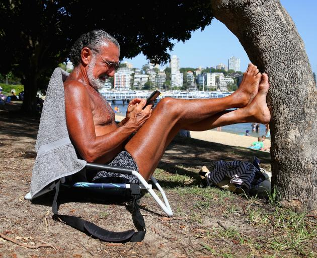 Sydneysider Ed Sciberras relaxes at Red Leaf Beach, as temperatuers across the state have...