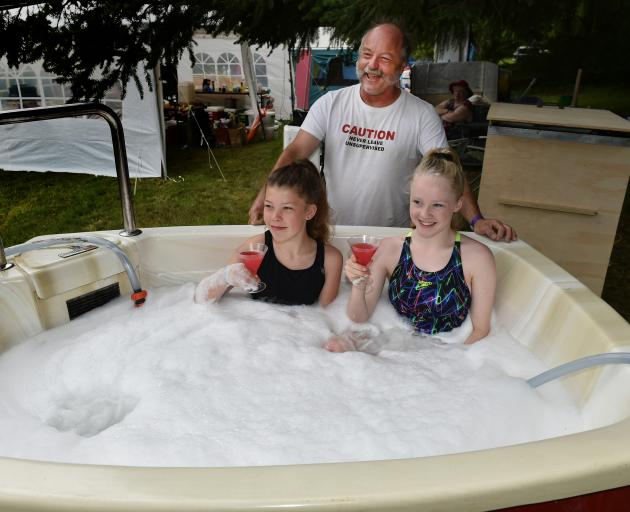 Talia Low (left) and Magic Chirnside (both 14) enjoy a mocktail in Neil George's portable spa pool during the Whare Flat Folk Festival yesterday. Photo: Gregor Richardson