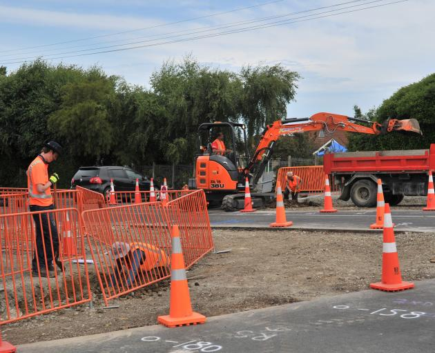 Contractors work on a roundabout and other safety improvements at the intersection of Brown St...