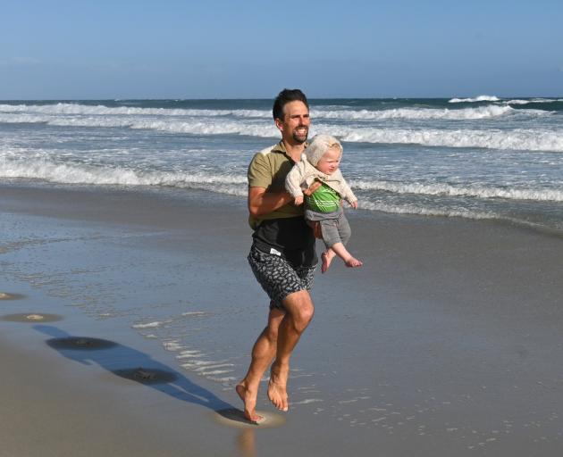 Matthew Onarheim-Smith runs along St Kilda Beach carrying his 14-month-old son Gabriel. Photo: Linda Robertson