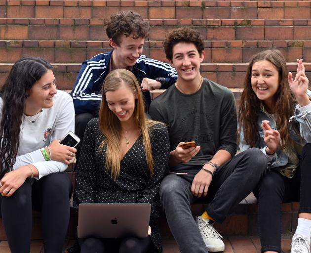 Sharing their NCEA level 3 results in Dunedin's Octagon yesterday, are (from left) former St Hilda's Collegiate pupil Lusia Maiai (18), former Logan Park High School pupils Bella Rennie (18), Quinn Hardie (rear, 17), Connor Vosh (18) and former St Hilda's