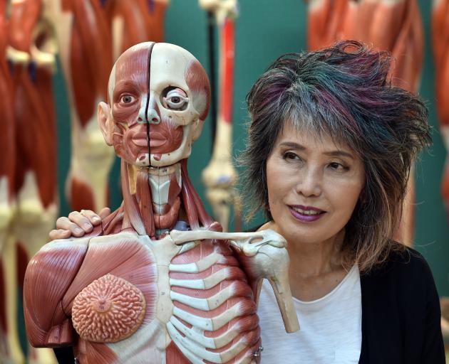 Thai forensic pathologist Porntip Rojanasunan inspects a plastic figure at the University of...