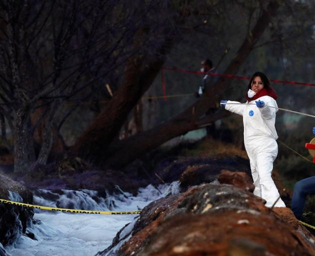 Forensic technicians work at the site where a fuel pipeline ruptured by suspected oil thieves exploded, in the municipality of Tlahuelilpan, state of Hidalgo, Mexico. Photo: Retuers