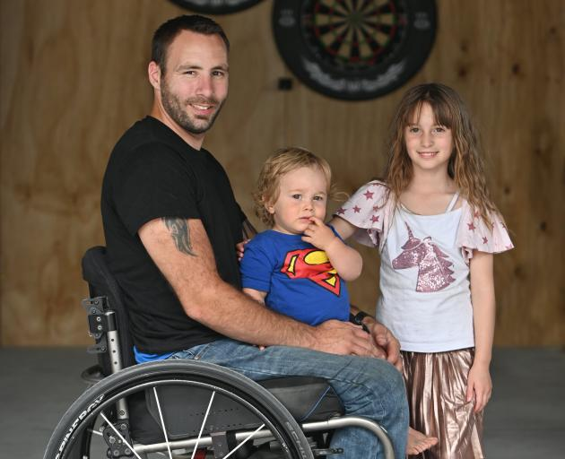 Disabled darts player Rob Gillan with children Connor (18 months) and Bailey (7) in his garage...