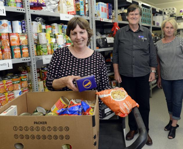Salvation Army volunteer Donna Dunford packs groceries as community ministries manager David...