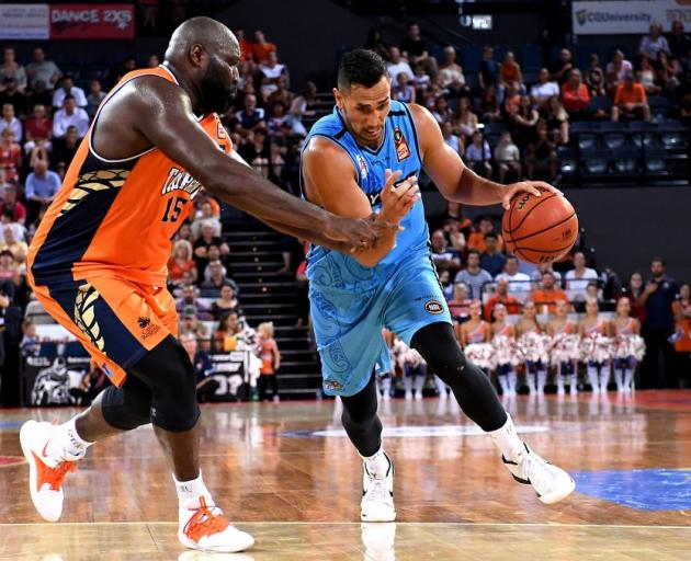 Tai Wesley attempts to drive past Nate Jawai during the Breakers game against the Cairns Taipans...