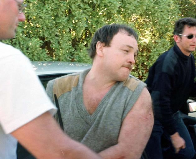 Arthur Taylor is escorted from the back of a police vehicle at the Tairua Police station in 1998 after surrendering to police in bush near Tairua after being on the run for nearly a week after escaping from Paremoremo Prison. Photo: ODT Files