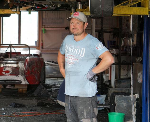 Andy Giles stands in front of a Rorstan Sports car, damaged in an early morning fire in Hawea Flat yesterday. Photo: Sean Nugent