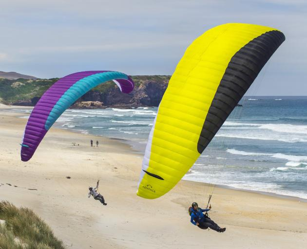 Roman Berner (left), of Switzerland, and Alex Tups, of Dunedin, model new paragliders as they fly...