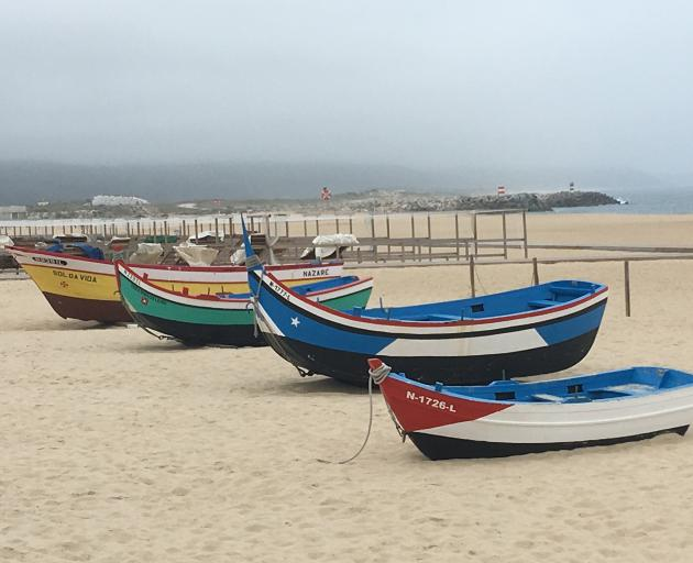 Colourful fishing boats sit on the beach. Photo: Pam Jones