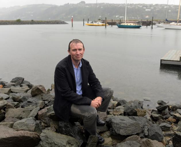 Chris Button sits beside Otago Harbour. PHOTO: LINDA ROBERTSON