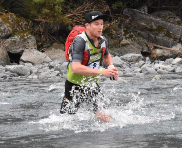 Dougal Allan crosses a stream during the mountain-running stage of the Longest Day at the...