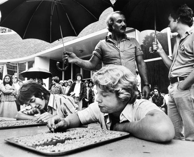 Students Frank Gwynne (left) and Donald Ellis pick at baked beans with toothpicks for an...