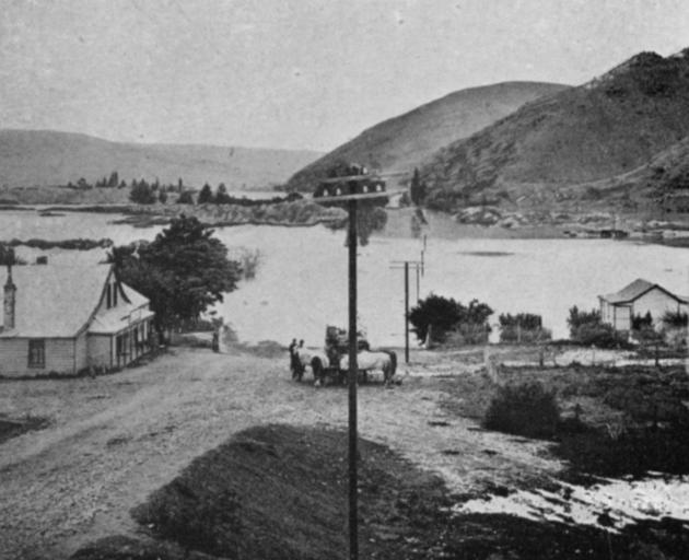 The flood at Ettrick, looking towards Millers Flat. The road bridge in line with the telegraph poles is completely submerged. - Otago Witness, 12.2.1919
