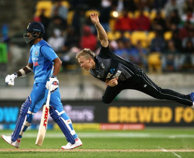 Scott Kuggeleijn of New Zealand bowls while Shikhar Dhawan of India looks on during game one of...