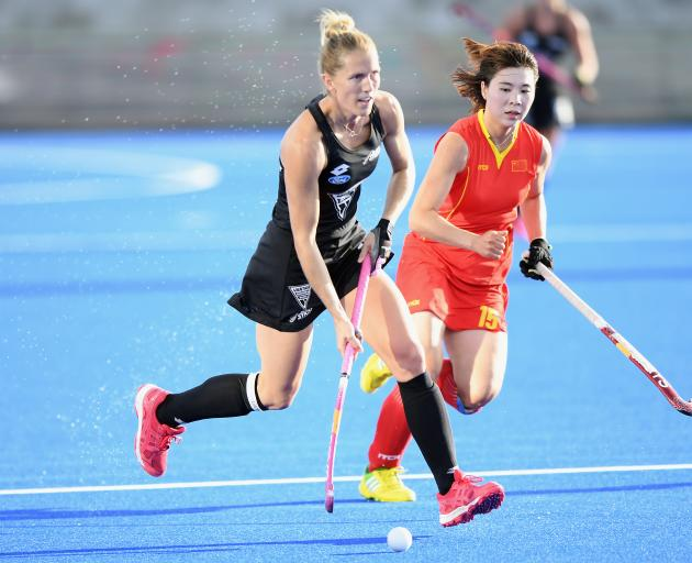 Stacey Michelsen, of New Zealand, controls the ball as she is pursued by Jinrong Zhang, of China,...