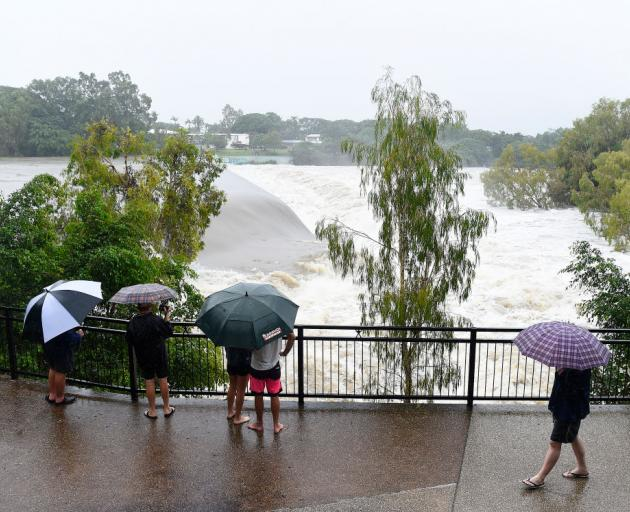Townsville Residents watch the raging floodwaters of the Ross River in the suburb of Douglas in...