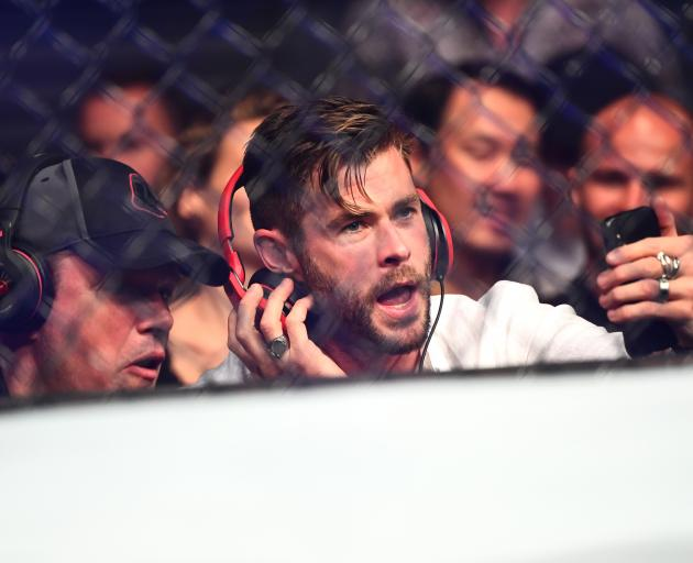 Matt Damon (left) and Chris Hemsworth watch on from ringside seats at UFC 234 in Melbourne. Photo...