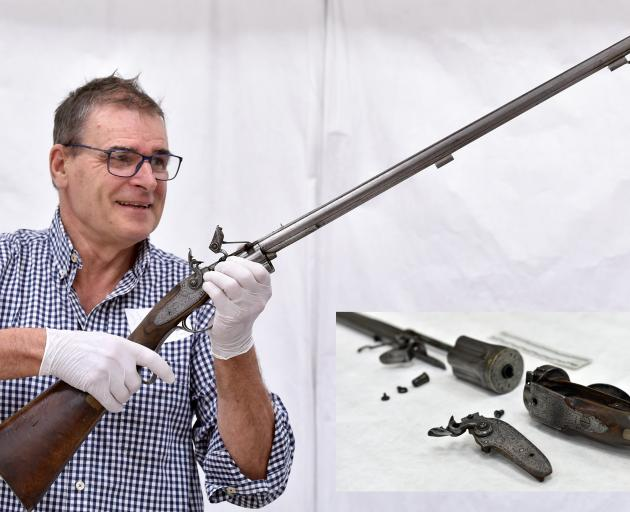 US researcher Ben Nicholson holds a 19th-century Collier revolving rifle, disassembled parts of...