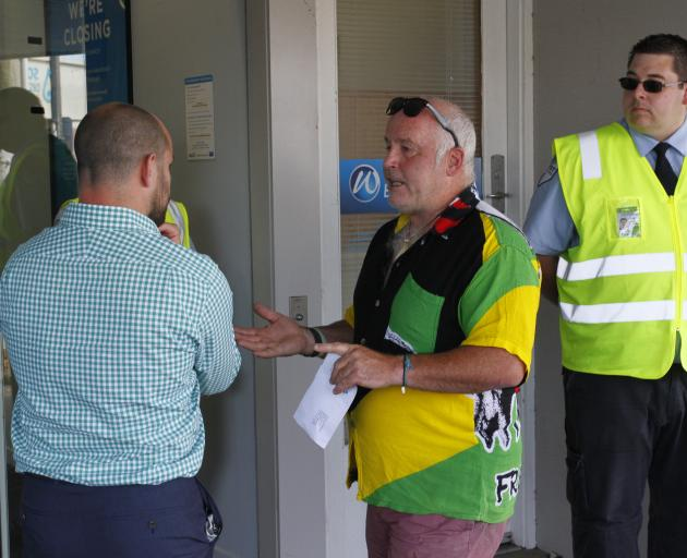 Riverton resident Wayne Hill (centre) speaks to an unknown bank member about the closure of the last bank in Riverton as a security guard looks on. Photo: Giordano Stolley