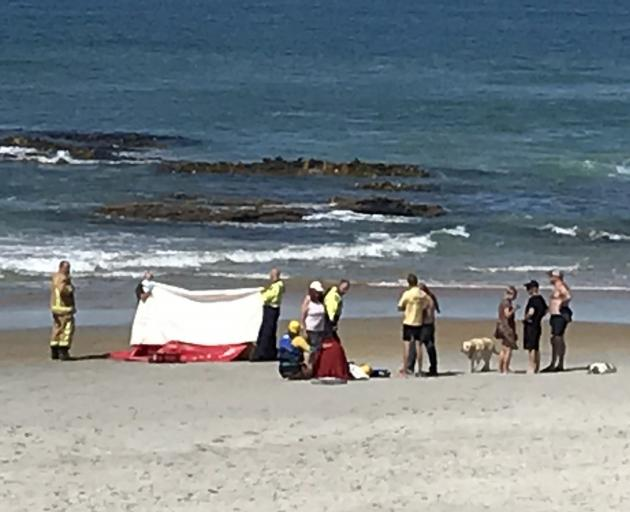 Emergency services and bystanders help one of the men who got into trouble at a beach near...