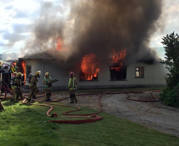 Fire crews work to control the fire raging though a four-bedroom homestead on Tokarahi-Tapui Rd...