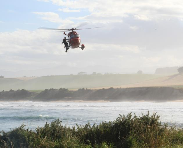 An Otago Rescue Helicopter circles back to land during a search for two missing men at Kakanui, yesterday evening. Photo: Hamish MacLean