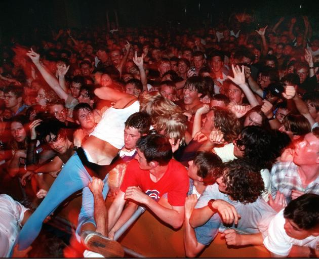 A stage diver is pulled from the crowd by security as Head Like a Hole play in 1999. Photo:...