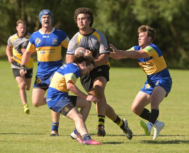 Vikings forward Josh Hill attempts to bust through some Taieri defenders in the final of the...