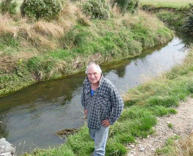 Ray McCrostie stands by the Waituna Stream which runs through his property. Photo: Ken Muir
