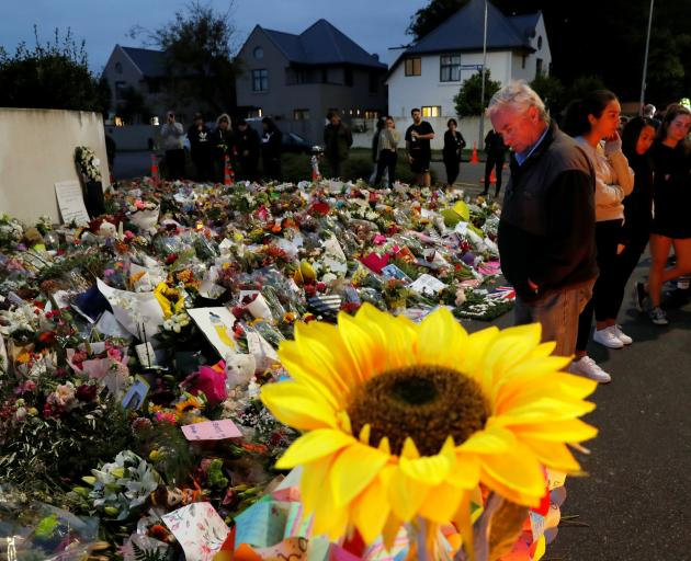 People pay their respects to the victims of Friday's shooting, in front of the Al Noor mosque in Christchurch. Photo: Reuters