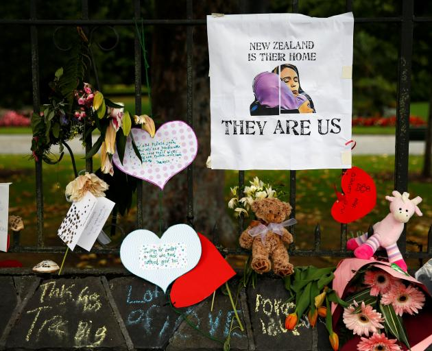 Flowers and signs are seen at a memorial site for victims of the mosque shootings, at the Botanic Gardens in Christchurch. Photo: Reuters