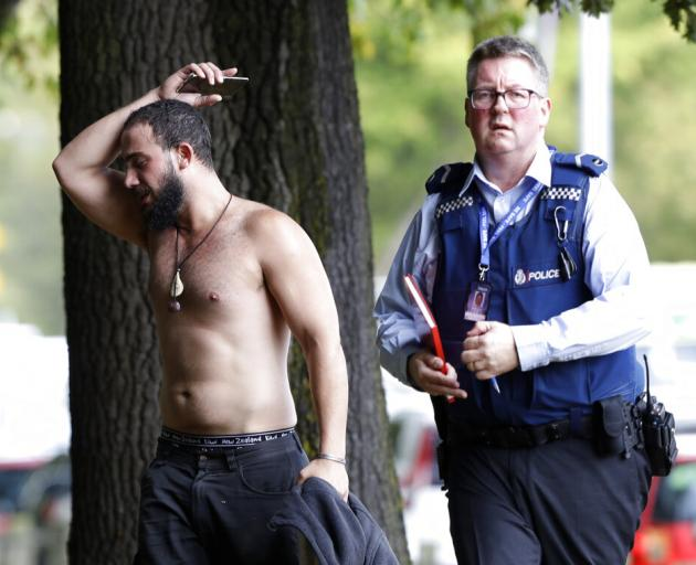 A police officer escorts a man away from a mosque in central Christchurch. Photo: AP