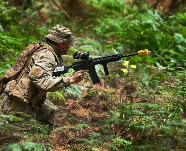 A Dunedin soldier scrambles through the undergrowth as he seeks a better position to cover his...