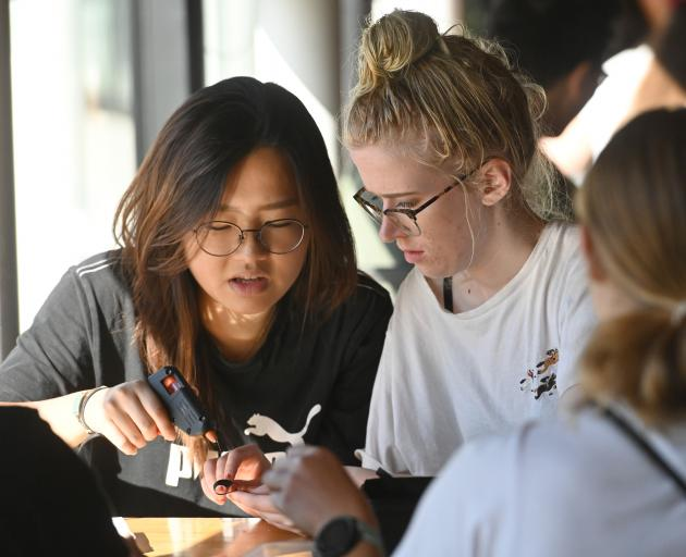 Yelin Seo (left) and Katie Ryan make black ribbons at the Otago Polytechnic Hub yesterday. PHOTOS...