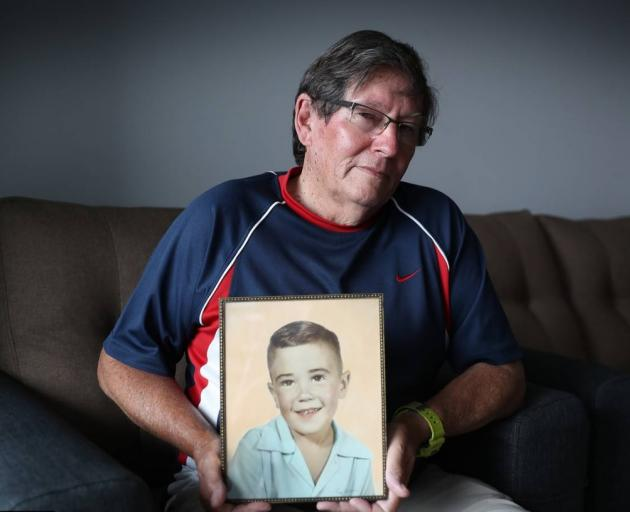 Gavin Boland holds a picture of his missing brother, Peter. Photo: NZ Herald