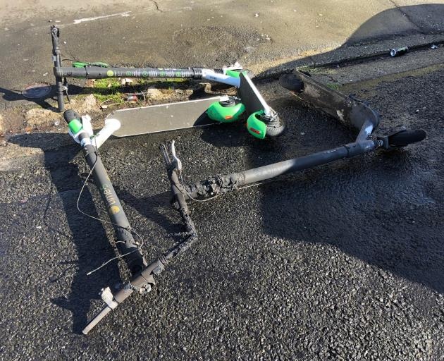 Three blackened Lime scooters lie on Leith St after being set on fire by drunken revellers yesterday. Photo: Chris Morris