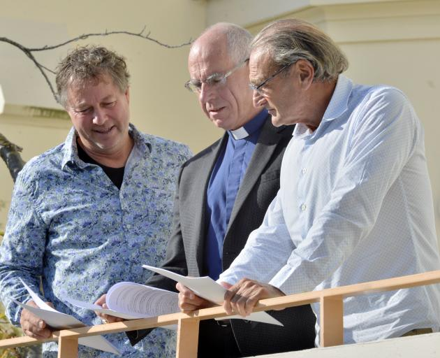 Catholic Bishop of Dunedin the Most Rev Michael Dooley (centre) reads a new memorandum of...