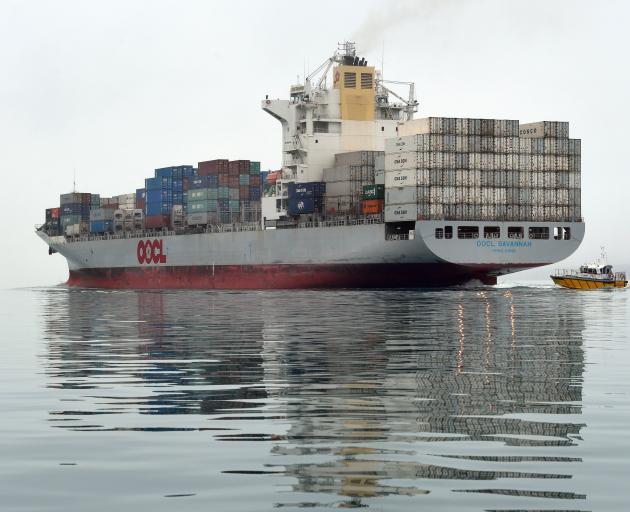The OOCL container ship Savannah, shadowed by Port Otago's pilot boat Aramoana, leaves Dunedin...
