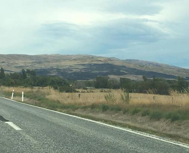 The dark patch on the hills shows were the fire raged overnight. Photo: George Block