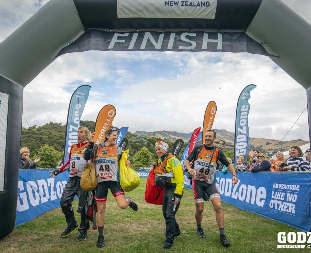 The winning foursome of (from left) Marcel Hagener, Emily Wilson and Simone Maier, all of Wanaka, and Chris Forne, of Queenstown, crosses the finish line at Akaroa yesterday to claim the Godzone adventure race. Photo: Alex Socci
