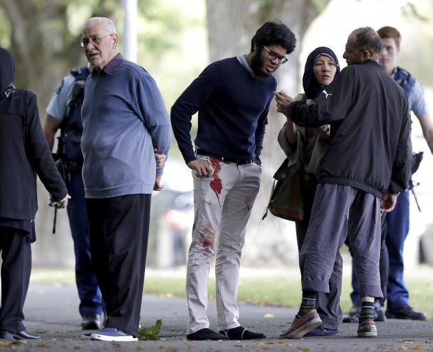A man with blood on his pants stands with a group of people across the road from a mosque in central Christchurch. Photo: AP