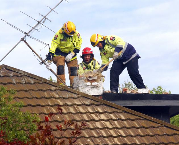 Firemen break down a chimney in a bid to gain access to a contractor, whose arm was pinned when...