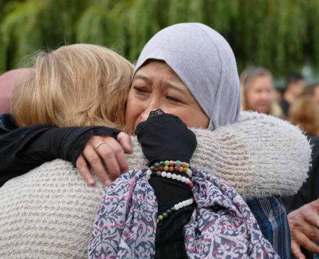 Maznab Abu Assan is embraced by Christine Adams, both of Queenstown, at the end of a candlelight vigil last night  Photo: Tracey Roxburgh